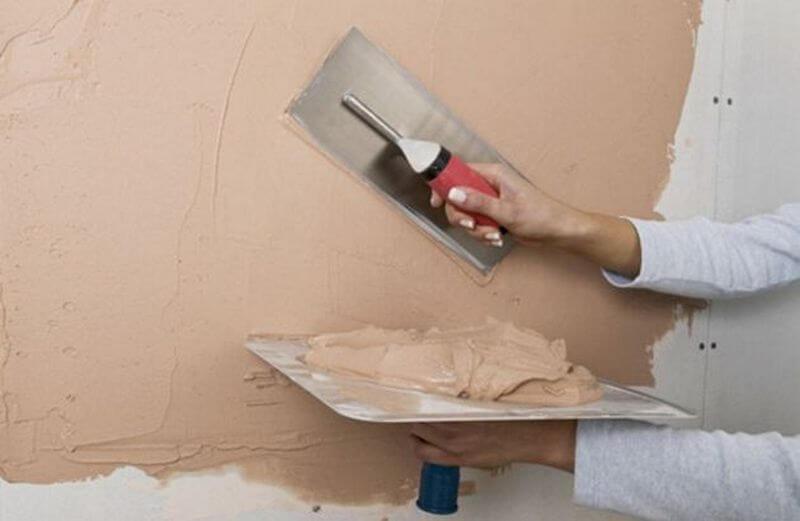 Нанесение строительной смеси на стену с помощью шпателя